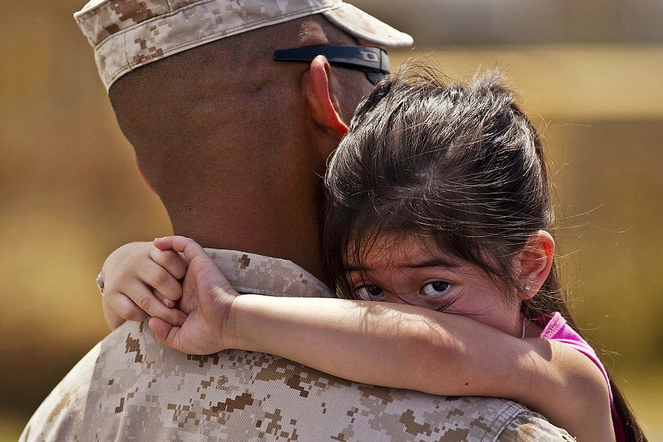 Photo of military person hugging girl